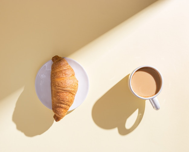 おいしいクロワッサンとベージュの背景にミルクとコーヒーのカップ