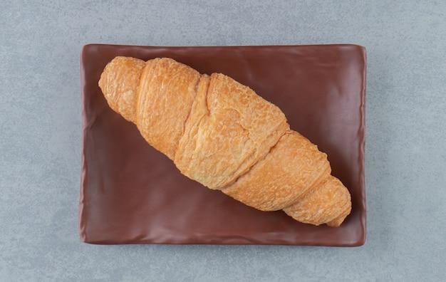 Delizioso croissant sulla piastra, sullo sfondo di marmo. foto di alta qualità