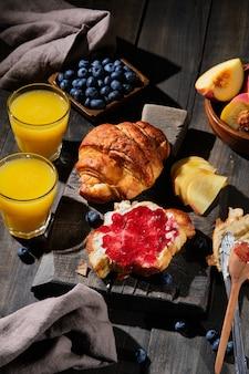 Вкусные круассаны на завтрак. свежая домашняя выпечка с ягодами, джемом, сливочным сыром и фруктами.