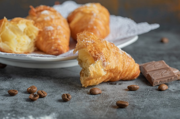 Delicious croissants with chocolate on gray.