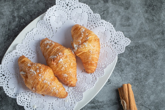 Delicious croissants with cinnamon sticks on gray.