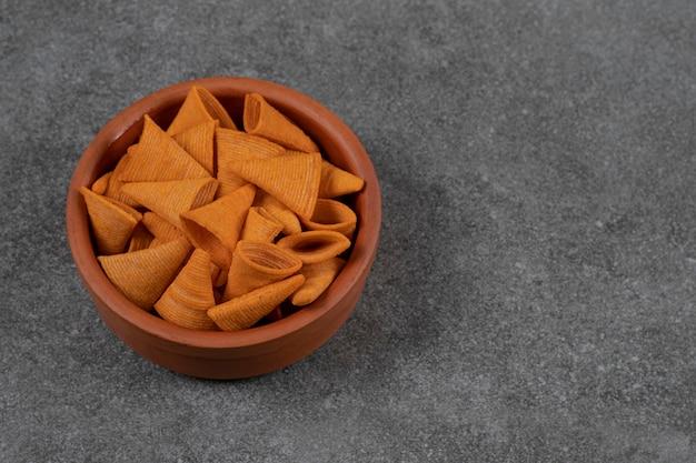 Deliziose patatine croccanti in ciotola di ceramica.