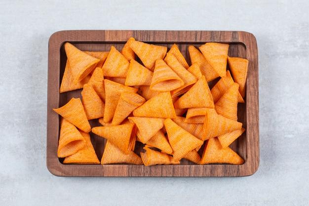 Вкусные хрустящие чипсы на деревянной тарелке.