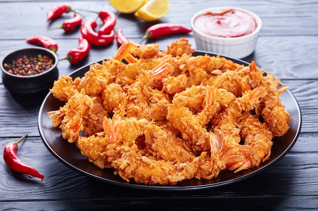 Delicious crunchy corn flakes breaded and deep-fried shrimps on a black  plate
