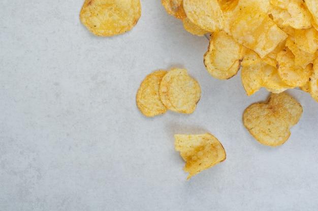 白い背景の上のおいしいカリカリポテトチップス。高品質の写真