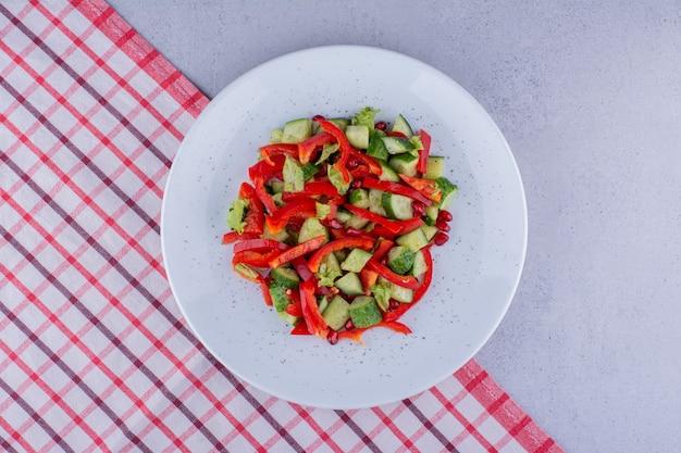 대리석 배경의 식탁보에 있는 맛있는 오이, 후추, 양상추 샐러드. 고품질 사진