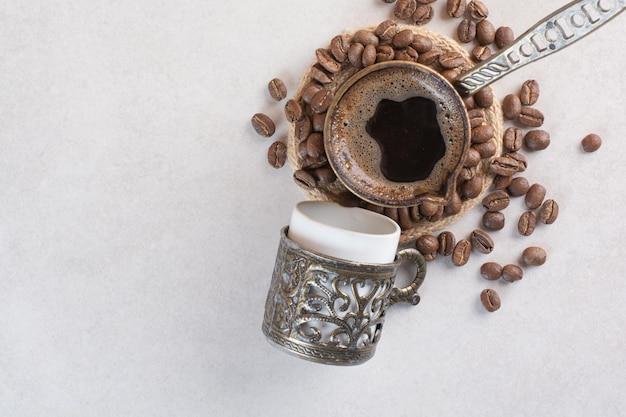 Вкусная чашка ароматного свежего кофе с кофейными зернами. фото высокого качества