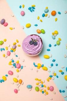 桃と青の背景に甘いキャンディーの近くのおいしいカップケーキ