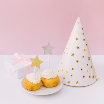 Delicious cupcake; party hat; gift box and muffins on white wooden surface against pink backdrop