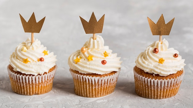Delicious cupcake wearing golden crowns