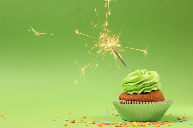 テキスト用のスペースと色の背景にキャンドルとおいしいカップケーキ