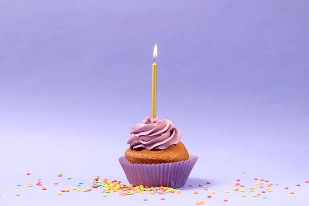 텍스트를 위한 공간이 있는 컬러 배경에 촛불이 있는 맛있는 컵케이크