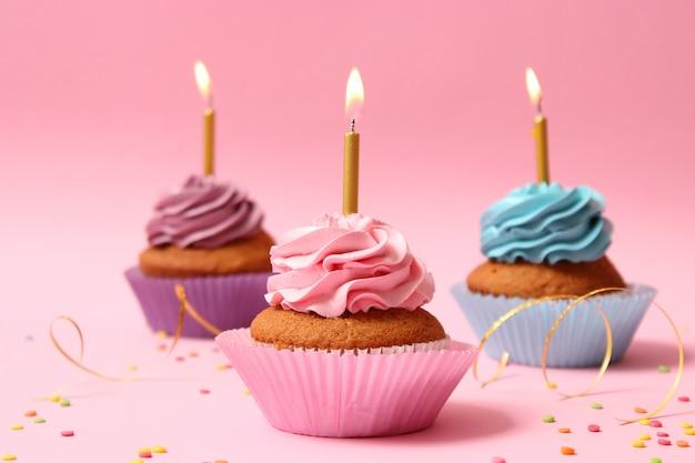텍스트를 삽입할 공간이 있는 컬러 배경에 촛불이 있는 맛있는 컵케이크. 축제 배경, 생일입니다. 고품질 사진
