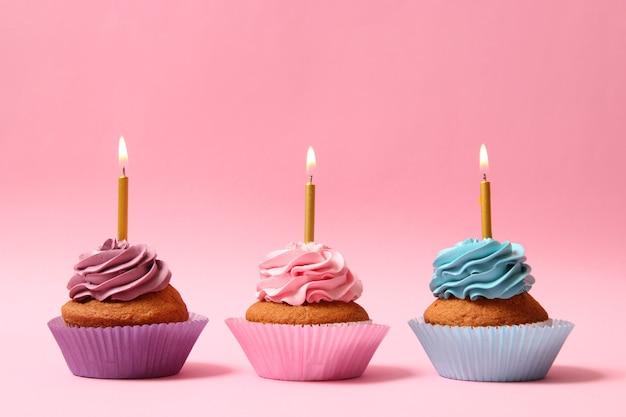 テキストを挿入するスペースのある色付きの背景にキャンドルとおいしいカップケーキ