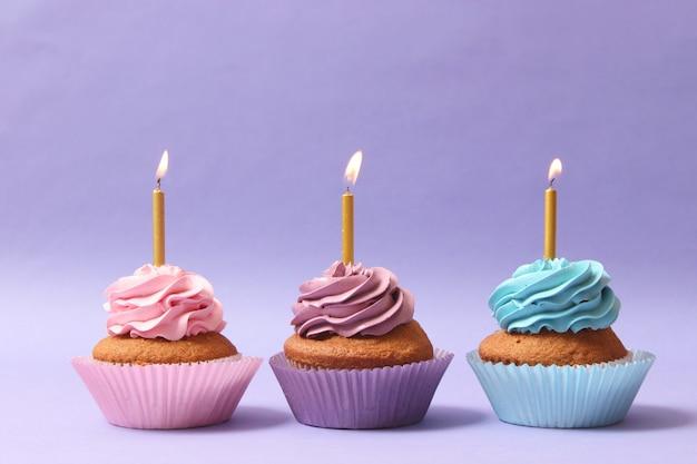 色付きの背景にキャンドルとおいしいカップケーキ