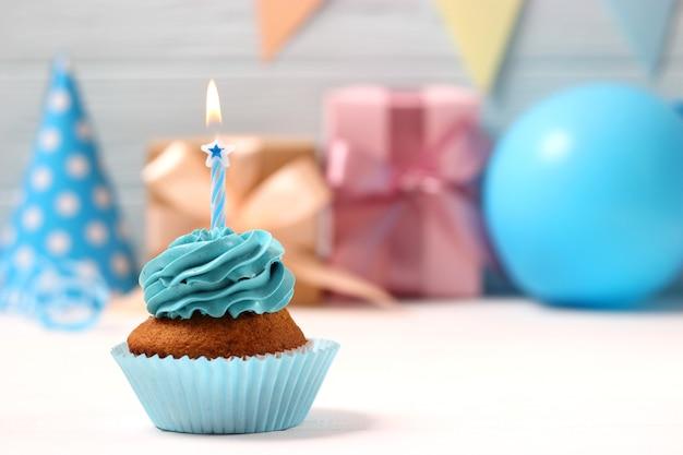 Вкусный кекс со свечой на цветном фоне