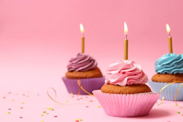 색색의 배경에 촛불이 달린 맛있는 컵케이크