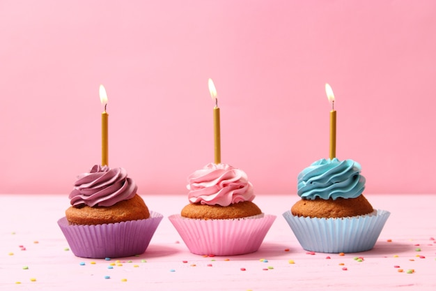 Delicious cupcake with a candle on a colored background with space to insert text. festive background, birthday. high quality photo