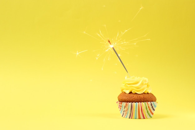Delicious cupcake with a candle on a colored background with space for text