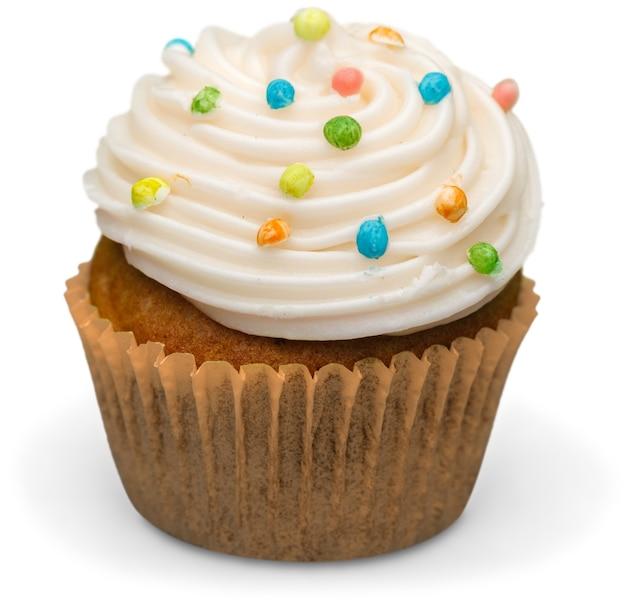 白い背景の上のクリームとおいしいカップケーキ