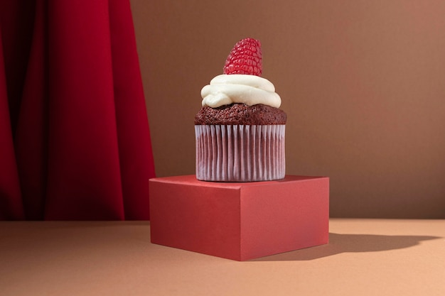 Delicious cupcake with cream and raspberry