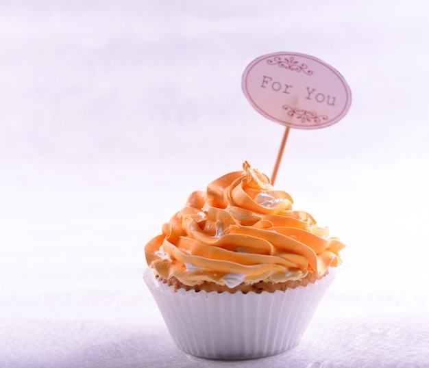 Вкусный кекс с надписью на столе на бежевом