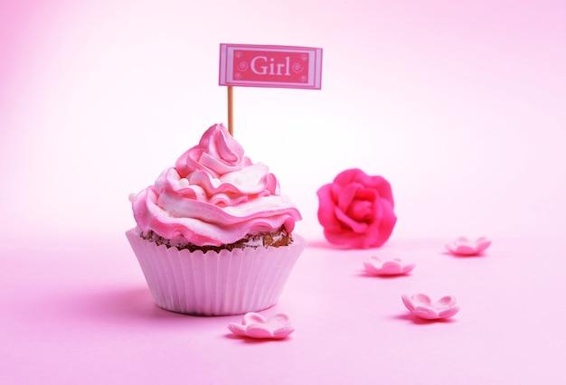 ピンクの背景のテーブルに碑文とおいしいカップケーキ
