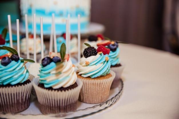 ベリーとおいしいカップケーキ。バタークリームと新鮮なラズベリー、ブルーベリーとカラフルなカップケーキ。特別な休日のお祝いイベント。子供たちのパーティー。お祝いテーブル