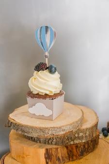 ベリーとおいしいカップケーキ。バタークリームと新鮮なラズベリー、ブルーベリーとカラフルなカップケーキ。特別な休日のお祝いイベント。キッズパーティー。