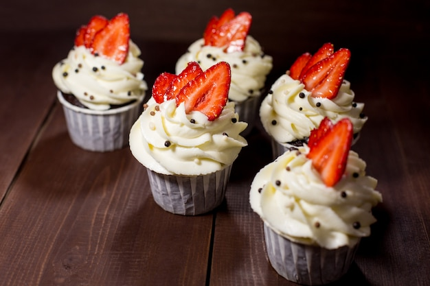 Delicious cupcakes with cream and strawberries.
