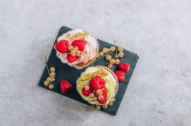 明るいベージュの背景の上に黒いスレートに新鮮なラズベリーとスグリのおいしいカップケーキ。テキストの場所を含む上面図