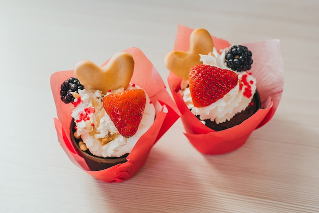 Delicious cupcakes with strawberries and blackberry berries and cookies