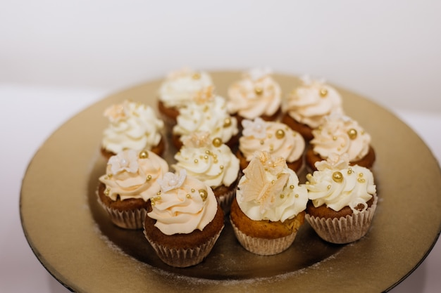 Delicious cupcakes with whipped cream on the golden plate