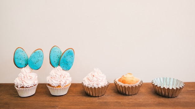 Delicious cupcakes with white cream and blue cakepops in row placed on wooden surface