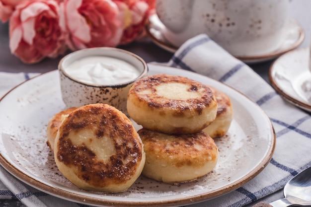 Вкусные творожные оладьи со сметаной. концепция завтрака или обеда. крупным планом