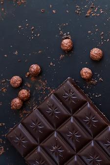 Вкусная плитка темного шоколада с стружкой, крошкой, рисовыми шариками, вид сверху на шиферный стол