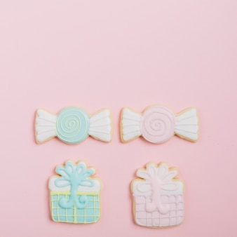 Delicious decorated cookies on pink backdrop