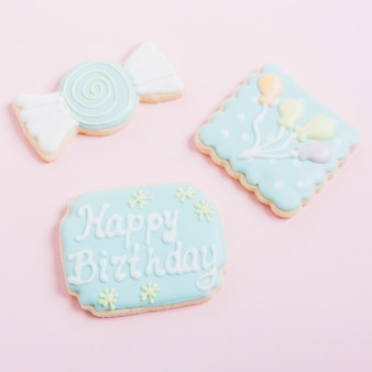 Delicious decorated cookies with different shapes on pink background