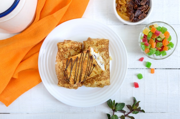 Delicious delicate pancakes with cottage cheese and raisins on a white wooden background.