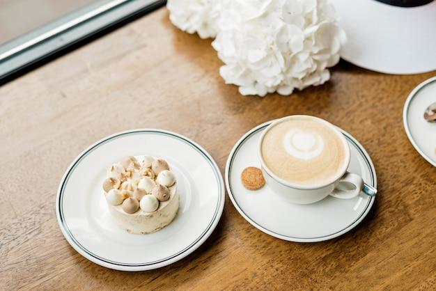 テーブルの上に美味しいデザートと一杯のコーヒー。コーヒーショップやレストランで焼きたてのデザートをお楽しみください。少し甘い装飾的なケーキとカプチーノのクローズアップショット。ソフトセレクティブフォーカス。