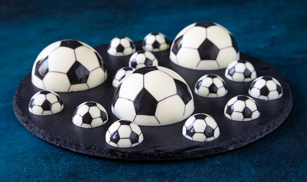 A delicious dessert of chocolate football balls of different shapes on a black serving plate - a concept of sports photography for a football fan