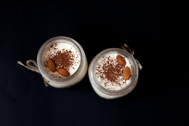 Delicious dessert in a glass jar on a black background, top view.