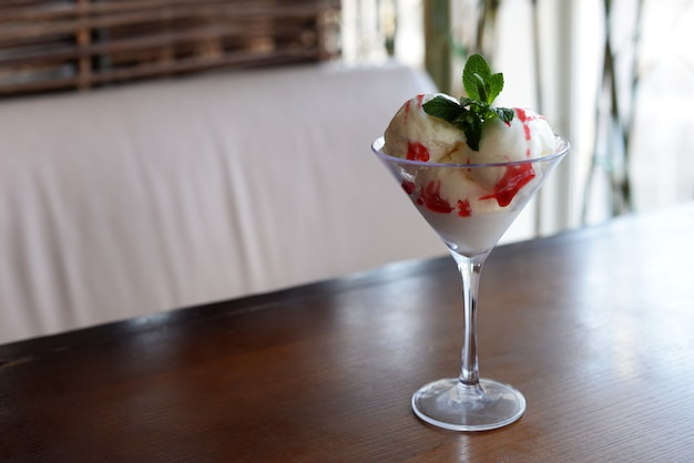 Delicious dessert ice cream with cream and strawberries jam andmint leaf in the restaurant