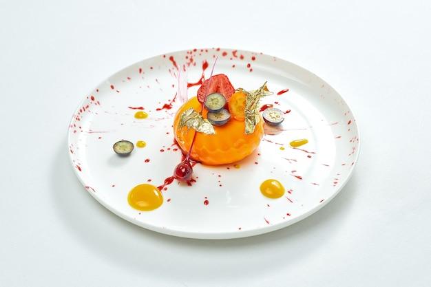 맛있는 디저트-베리 작성 및 카라멜과 베리 장식 하얀 접시에 망고 무스. 회색 표면에 절연.
