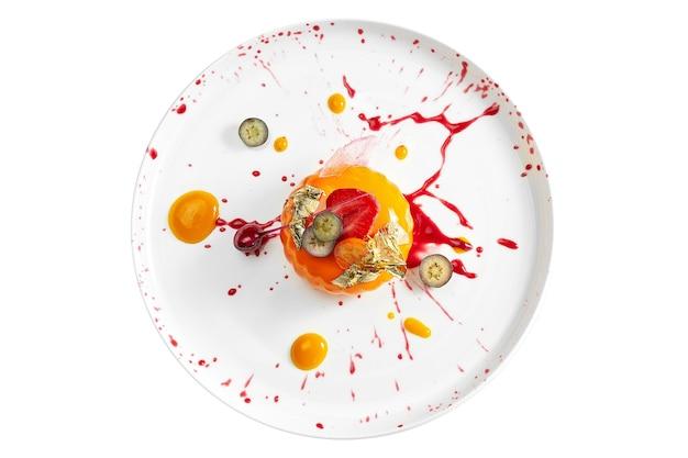 맛있는 디저트-베리 작성 및 카라멜과 베리 장식 하얀 접시에 망고 무스. 흰색 표면에 격리. 위에서보기