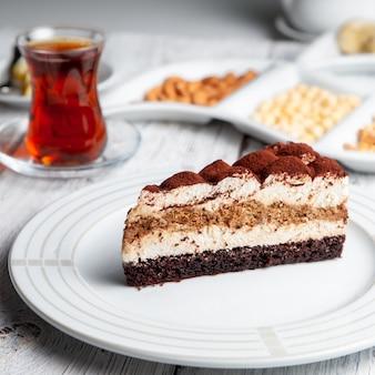 Dessert delizioso in un piatto con tè, vista matta dell'angolo alto su un fondo di legno bianco