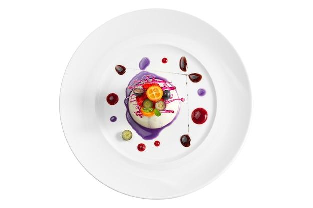 맛있는 디저트-베리 작성 및 카라멜과 베리 장식 하얀 접시에 바닐라 무스. 흰색 표면에 격리. 위에서보기