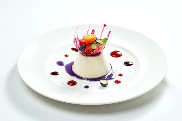 맛있는 디저트-베리 작성 및 카라멜과 베리 장식 하얀 접시에 바닐라 무스. 흰색 표면에 격리.