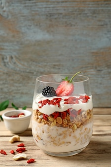 Delicious dessert with goji berries in glass on wooden background