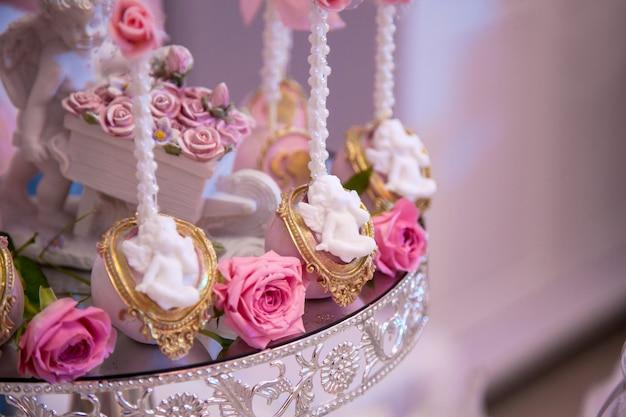 Вкусные десерты в свадебном моноблоке в зоне фуршета: шоколадные конфеты, украшенные ангелочками и камеями, и свежие бутоны роз.